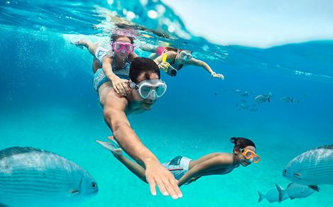 A family of four snorkeling with fish at CocoCay