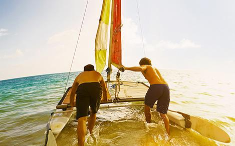Two friends pushing a sailing boat in the water during cruise vacation.