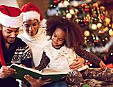 Family wearing Santa Hats Reading a Story with Christmas Tree in the Background