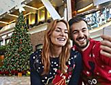 Couple Taking a Selfie with a Christmas Tree in the Background as part of the Holiday Cruise Experience