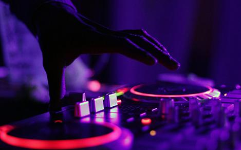Hand of a DJ playing music at one of many cruise nightclubs and poolside parties.