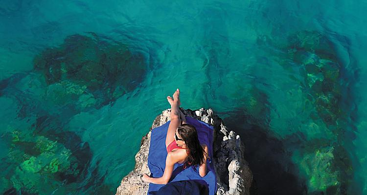 WOW Hero image from Oasis and Caribbean shoot, woman lying on blue beach towel on rock jutting out into ocean, sunbathing, surrounded by gree-blue water, rocks underwater, Labadee, Haiti,  NO TV BROADCAST OR CINEMA PLACEMENT IS ALLOWED.