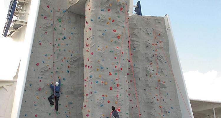 Passengers or people or men and women climbing onboard or on board rock wall or Rock Climbing Wall. Sport, activity, harness, ropes, outdoors, climb. Freedom of the Seas?, Freedom class, FR