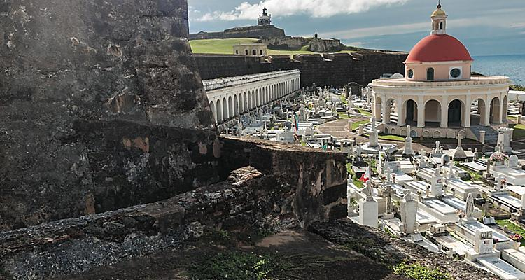 Glimpse of Hawaii, GoH influencers, Sage Stephens, Puerto Rico, young woman standing on top of old wall, building, overlooking city of San Juan, church in background, fun, adventure, culture,