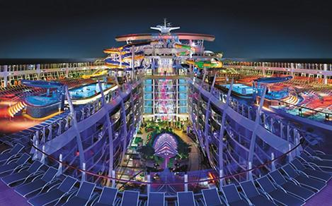 HM, Harmony of the Seas, OOH, wide panoramic view of top deck with the Perfect Storm water slides in center, night, nighttime, top deck with pools, Central Park below, night sky in background, purple, blue colors,