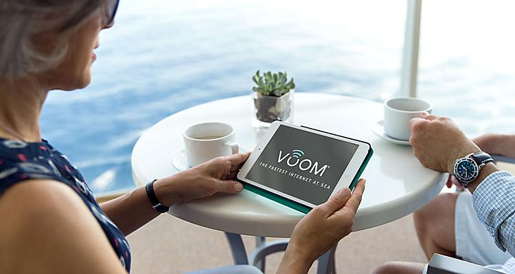 OA, Oasis of the Seas, Royal Suite Class, GENIE shoot, couple on balcony having coffee, woman holding tablet with VOOM interface, internet, wifi, technology, broadband, web, connectivity, ocean in background,   NOTE: This version has the revised and updated VOOM logo as of March 2017, now with trademark symbol instead of service mark. (This change is very small in the photo, not really visible in small web images.)   This file is a jpeg. For high-res tif, open Related Assets container below.