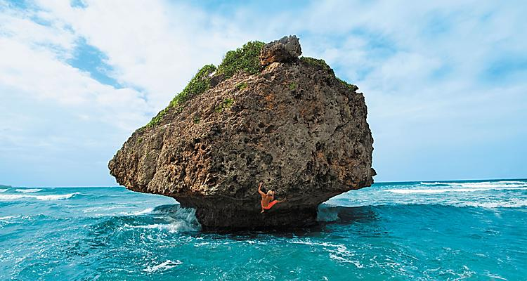 Glimpse of Hawaii, GoH influencers, Nate Ancheta, Barbados, wide shot of young man climbing large coral rock, clinging to side of boulder in ocean, athletic, daring, fun, adventure, strength,