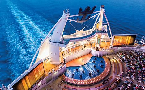 """HM, Harmony of the Seas, Aqua Theater show, """"A Fine Line"""", view from above, performers on stage, audience, movie screens on sides, wake of ship in back, night shot, crown and anchor logo in rigging above,"""