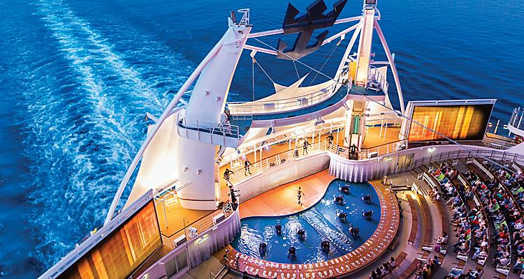 "HM, Harmony of the Seas, Aqua Theater show, ""A Fine Line"", view from above, performers on stage, audience, movie screens on sides, wake of ship in back, night shot, crown and anchor logo in rigging above,"