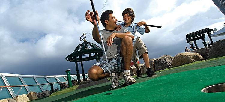 onboard or on board, ship or boat, father, son, mini, miniature golf, railing, putting green, balls, sports, fun, club.  US Hispanic or USH or latin onboard or on board, voyager of the seas, voyager class, vy