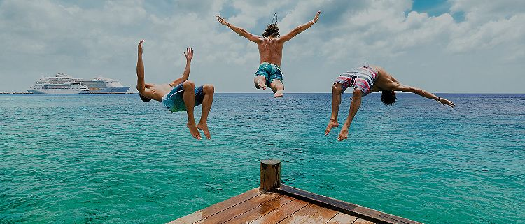 Friends jumping off a dock into the ocean