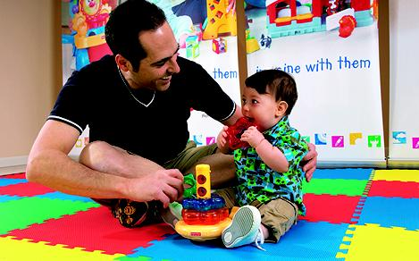 Father and son playing in a playroom onboard a family-friendly cruise.