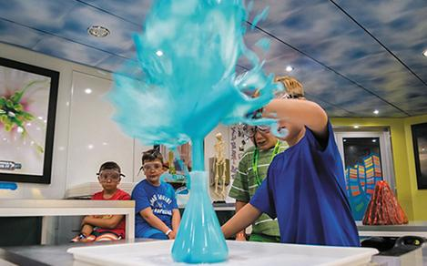 Kids playing with a volcano experiment at the Adventure Ocean Lab