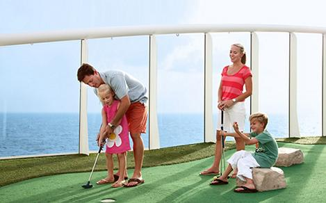 Family playing mini golf on a cruise. A cruise activity for families with children.