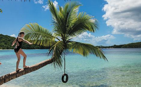 "the Vons, von Niederhausern family, ""8 Hours In"" shoot, fun, St. John beaches, young girl and young boy walking on horizontal palm tree trunk on beach, tire swing hangs from tree, seaside, shoreside, seashore"