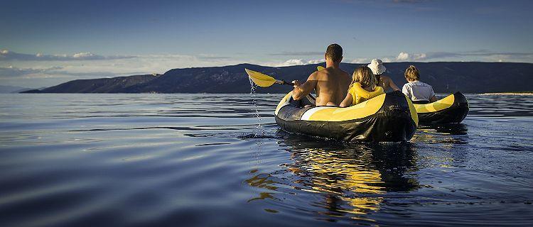 Panoramic shot of young family enjoy sea kayaking, rear view.