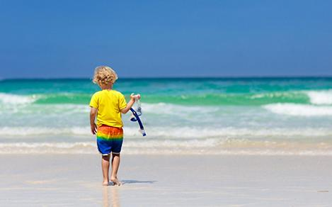 Child snorkeling on tropical beach. Kids snorkel in ocean on family summer vacation on exotic island. Little boy playing with water and sand at sea shore. Toddler running in waves. Beach fun for kid.