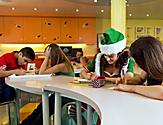 Oasis of the Seas, holiday, teens at tables in Adventure Ocean, father and son in background, family, young woman wearing green Santa''s elf outfit, hat and jacket, writing, coloring, drawing, fun