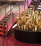 HM, Harmony of the Seas, Medusa''s Shoes, Artwork, Deck 4 Forward, artist John Breed, art, gold sculpture of legs, feet with shoes, next to red stairway in Entertainment Place, no people,