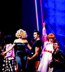 Performers singing and dancing on stage to the Grease Broadway show on Harmony.