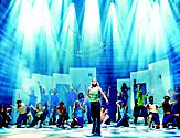Woman standing on main stage with lights during a Mamma Mia broadway show onboard Allure