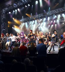 Crowd of Rockers on brightly lit stage during We Will Rock You Broadway show onboard a cruise ship.