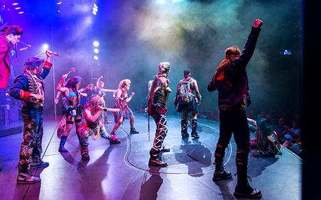 A gang of rockers on stage with their fists up during a We Will Rock You broadway show on a cruise.
