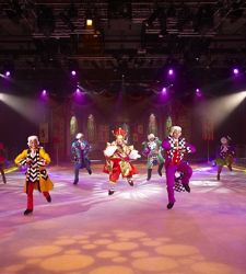 Performers dancing in colorful costumes during ice skating shows onboard a cruise.