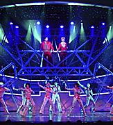 Performers in brightly lit stage during the All Access Cruise Show.