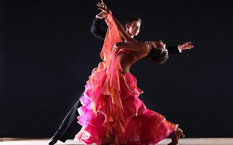 A tango couple dancing for the Bailamos Cruise Show featuring a woman in a hot pink ruffled dress and a man in a suit.