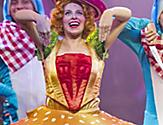 Performer in hamburger costume smiling on stage during the Columbus Musical Cruise Show