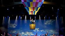 Performers jumping on stage with hot air balloon above during the Come Fly With Me Cruise Show on Oasis of the Seas