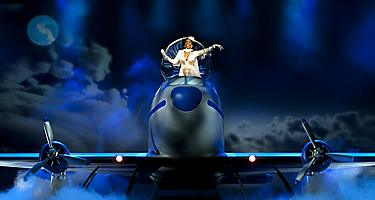 Airplane on stage with performer in it during the Come Fly With Me Cruise Show on Oasis of the Seas