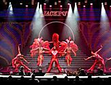 Performers in red costumes on stage during the Jackpot Cruise Show on Adventure of the Seas