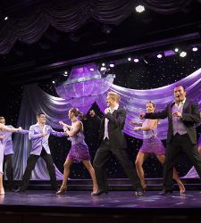 Performers dressed in purple dancing on stage during an original production cruise show by Royal Caribbean