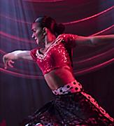Salsa dancer on stage during an original production cruise show by Royal Caribbean