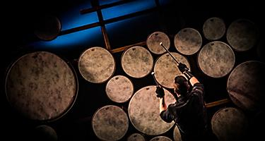 A man is drumming during the Sonic Odyssey Cruise Show by Royal Caribbean