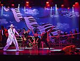 Performers dancing in piano background stage during the Legend of the Seas Cruise Show