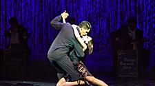 Couple dressed in black dancing on stage during the Tango Buenos Aires Cruise Show on Jewel of the Seas