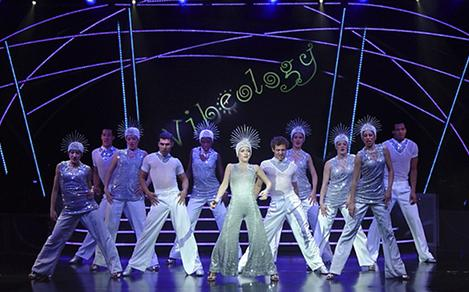 Performers dressed in white on stage during the Vibeology Cruise Show on Serenade of the Seas
