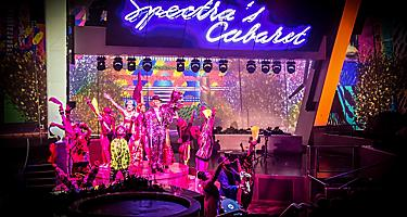 Performers on stage with pink lights at night show of Spectras Cabaret on Anthem.