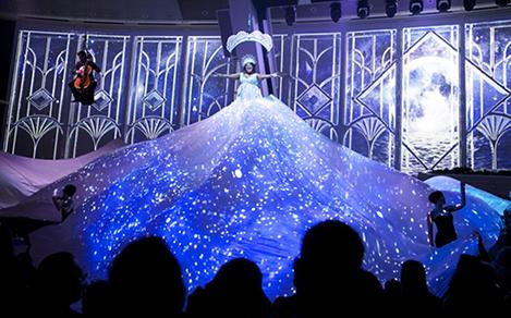 Singer on stage wearing a huge dress skirt that glows blue during Starwater acrobat show on Quantum.