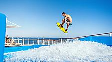 HM, Harmony of the Seas, instructor, man doing a high jump, jumping on Flow Rider, onboard surfing, surf, waves, fun, action, excitement, athletic, athlete, horizon, ocean view in background,
