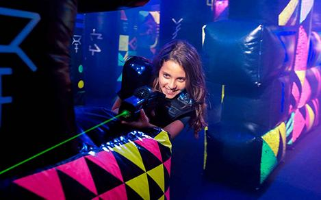 A girl aiming her laser at another player while playing laser tag onboard a cruise ship