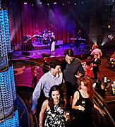 Two couples at Music Hall on QN, nightlife, live music, night time, entertainment, adults on stairway at Music Hall, band playing in background