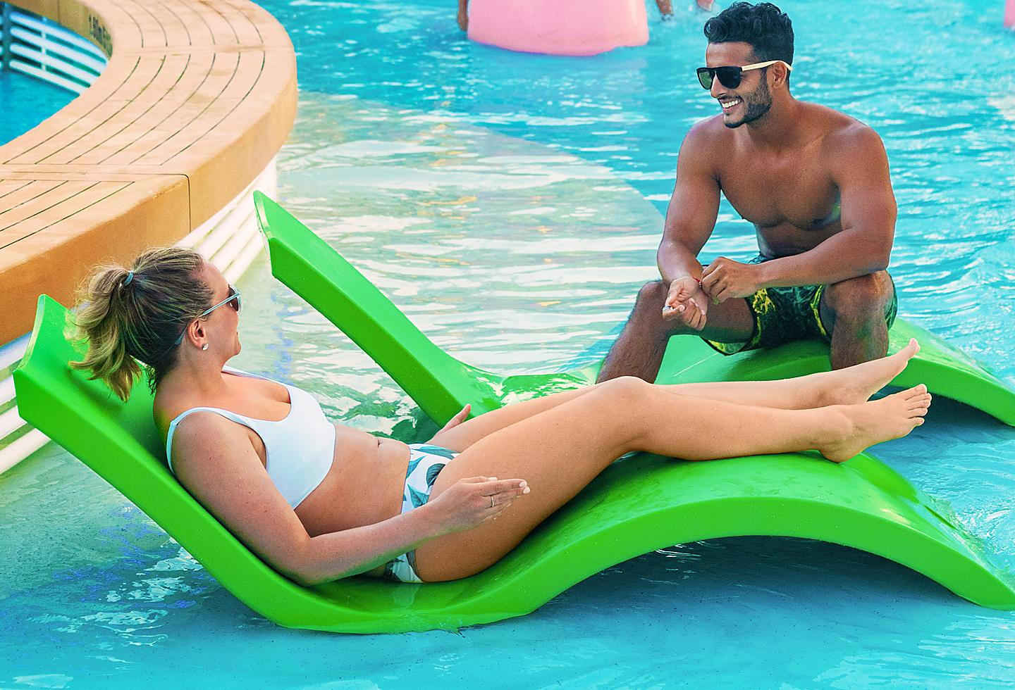 Couple tanning by the pool onboard Navigator of the Seas