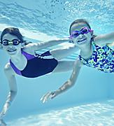 Girls Diving and Swimming in the Covered Pool