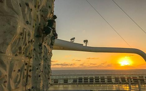 Man Climbing The Rock Wall During Sunset