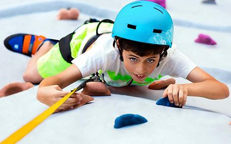 Young Boy Reaching the Top of the Rock Wall