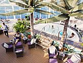 Oasis Suite Class lifestyle images, Solarium, pool, people lounging, relax, relaxing, lounge chairs, server, waiter, serving drinks,